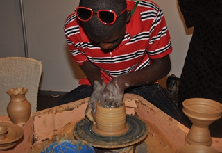 Exhibitors moulding local pots at the trade fair